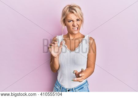 Young blonde girl wearing casual clothes disgusted expression, displeased and fearful doing disgust face because aversion reaction. with hands raised