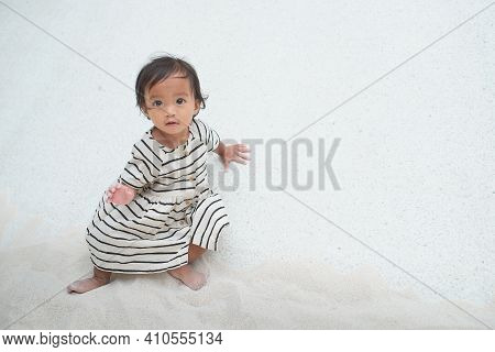 Cute Asian 1 - 2 Years Old Toddler Baby Girl Child Playing With Sand In Sandbox At Public Playground