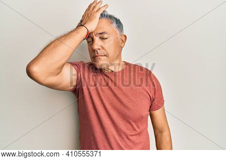 Handsome middle age mature man wearing casual clothes surprised with hand on head for mistake, remember error. forgot, bad memory concept.