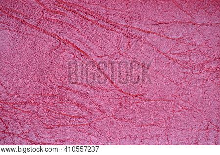 A Fragment Of Genuine Leather With Wrinkles And Folds, Artificially Dyed In A Bright Crimson Color.