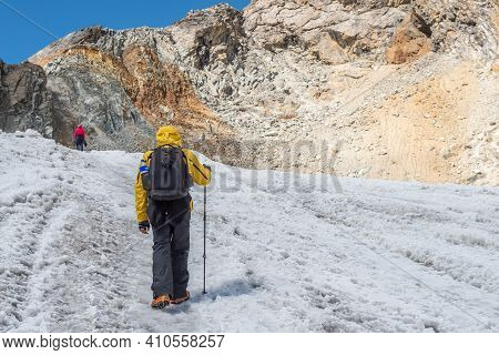 Back View Of Trekker Hiking On The Slope Of Chola Pass Glacier For Ascending To The Top Of Chola Pas