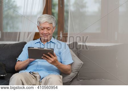 Asian Senior Men Using Tablet At Home. Asian Senior Chinese Male Search Information About How To Goo