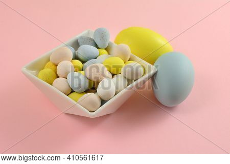Pastel Colored Candy Easter Eggs In White Dessert Bowl With Two Painted Easter Eggs On Pink Backgrou