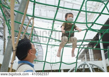 Cute Little Asian Boy Child Wearing Washable Face Mask Climb On Jungle Gym At Pulbic Indoor Playgrou