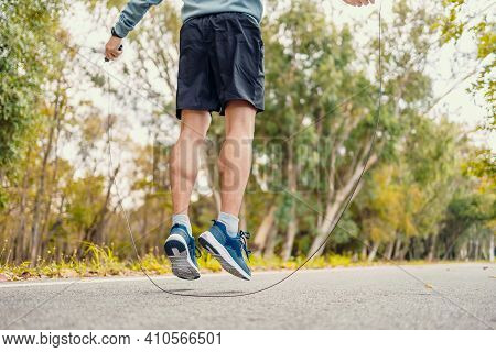 Male Feet Jumping In Mid Air Whilst Using A Skipping Rope, Jump Rope In The Park.
