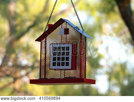 A Red House Shaped Suet Bird Feeder Filled With Birdseed