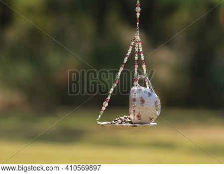 A Pink Teacup Bird Feeder With Seed Hanging In The Yard