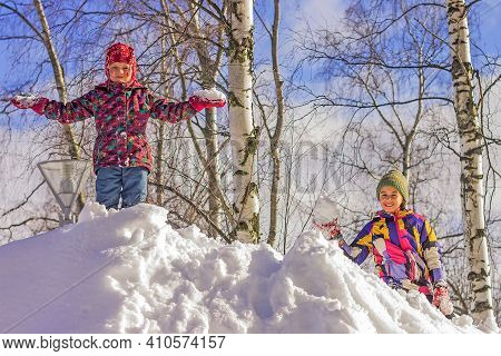 Snow Winter Fun. Girls Play On A Walk On A Large Snowdrift.