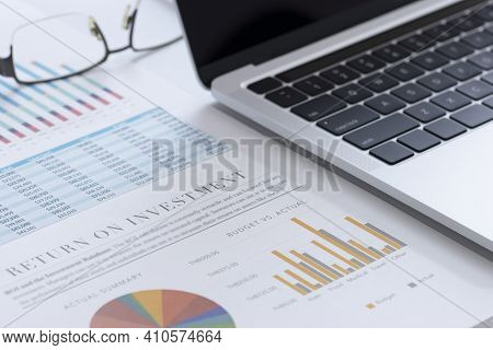 Closeup Of Laptop Or Notebook Computer And Financial Reports With Colorful Charts, Graphs And Diagra