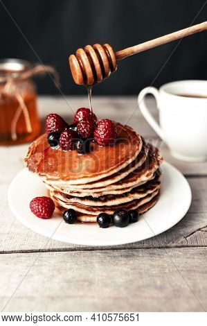 Pancakes With Berries And Honey On A White Plate, Wooden Spoon, Jar, Coffee Cup