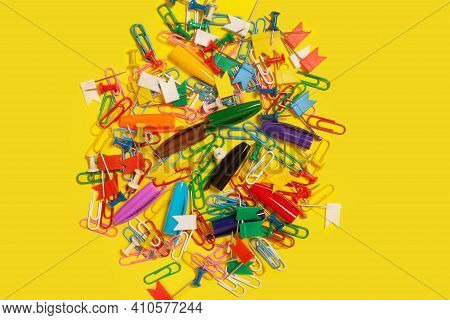 Pile Of Colored Pushpins, Paper Clips And Pen Caps Lying On A Yellow Background. Free Copyspace