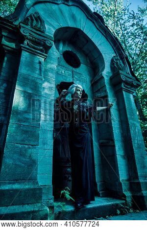 An aristocratic old widow woman with beautiful gray hair and a rich black dress stands sad in a crypt in a cemetery. Black Widow. Atmosphere of mysticism. Halloween.