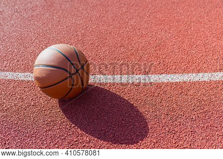 Orange Ball For Basketball Lying On The Sport Court.sport Red Court Outdoor .copy Space.top View.