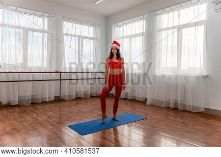 A Young Woman Fitness Instructor In Santas Hat And Red Sportswear Leggings And Top Stretching In The