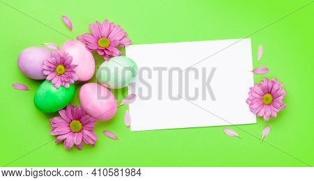 Easter greeting card with colorful easter eggs and flowers. Top view flat lay with space for your greetings