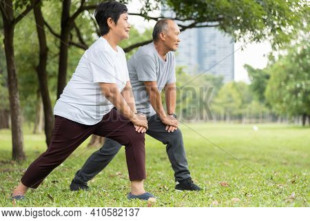Asian Senior Man And Woman Doing Exercise At Park. Happy Elderly Couple Enjoying Workout At Outdoor