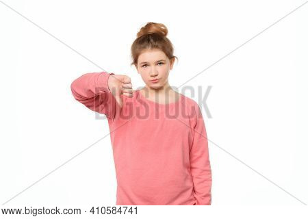 Displeased Teen Girl Isolated On White Background Showing Thumb Down With Negative Expression, Gestu