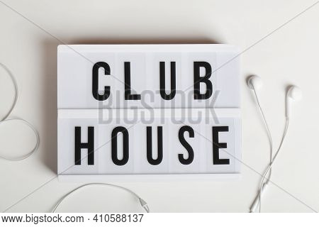 White Headphones And Lightbox With Text Clubhouse On White Background. Top View Flat Lay