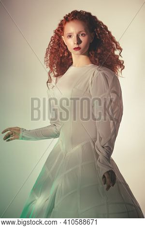 Art portrait of a refined fashion model girl with lush red curly hair posing in a white haute couture dress. Studio shot.
