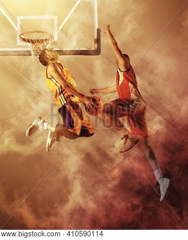 Two basketball players in action on smoke background. Blocked shot