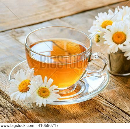 A Cup Of Herbal Tea On A Wooden Table, Wild Chamomile Flowers, A Warm Relaxing Drink Made From Natur