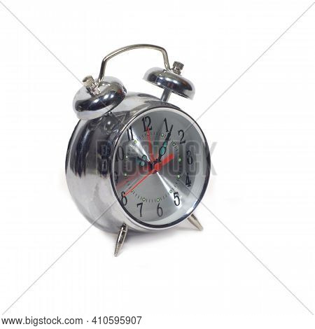 Table alarm clock in silver stainless steel case with a round shape of the dial, showing five minutes past ten isolated on a white background side view closeup