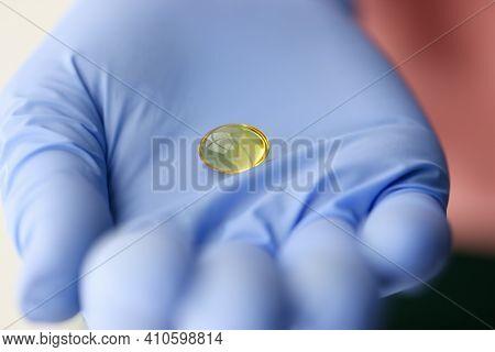 Yellow Capsule Of Vitamin D Lying On Doctors Hand Closeup. Preventive Vitamin Intake Concept