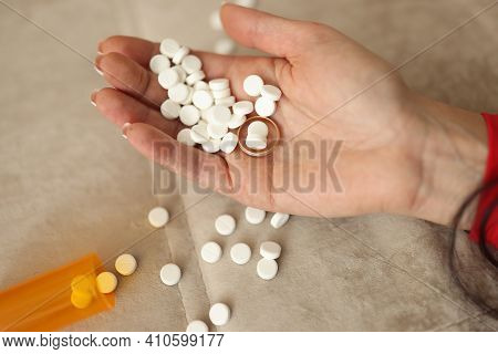 Many White Pills And Wedding Ring Lying On Womans Hand Closeup. Male Infidelity Concept