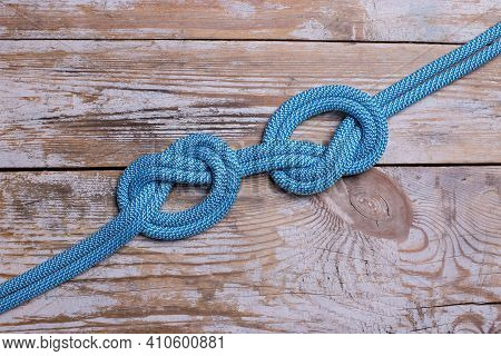 A Knot On A Rope On A Wooden Background. Two Knots On A Blue Rope.