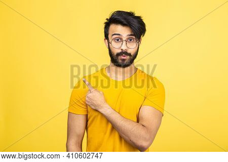 Emotional Portrait Of A Hindu Man In A Yellow T-shirt On A Bright Orange Background.