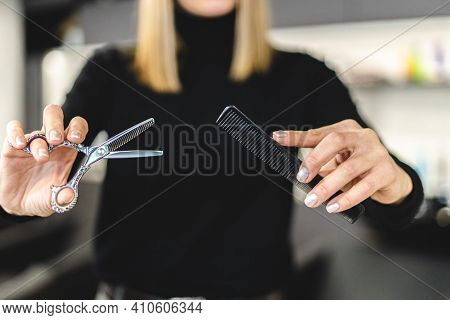 Hair Stylist Woman Hands Hold Scissors And Comb Close-up. Hairdressing And Hair Care