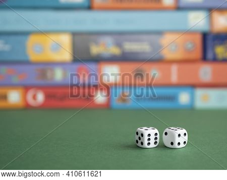 Two Dice On The Background Of Board Game Boxes. Dice Games For Kids, Tweens And Adults