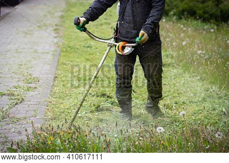 Closeup Of A Worker In Protective Clothing, Gloves, Rubber Boots With A Lawn Mower On The Front Lawn
