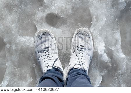 Feet In Wet Sneakers Standing In The Melted Snow. Puddles, Thaw, Muddy Underfoot On The Sidewalk. Fi