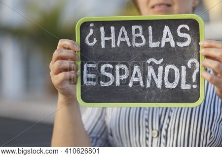 Woman Holding A Chalkboard With The Question Habla Espanol? Do You Speak Spanish? Written In Spanish