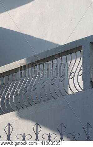 Low Angle View Of Vintage White Balustrade On Terrace With Sunlight And Shadow On Surface Of The Old