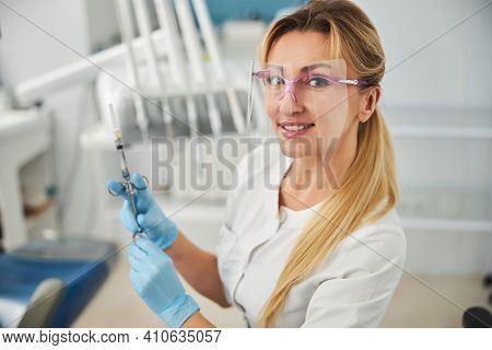 Stomatologist In Face Shield Pressing A Dental Syringe