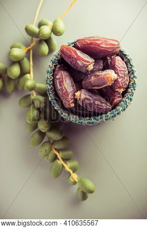 Bowl of ripen dates along with bunch of young, green dates. Ripen and green dates.