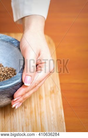Vertical Image Of Female Hand Holds Mortar With Dry Pepper On A Wooden Kitchen Board