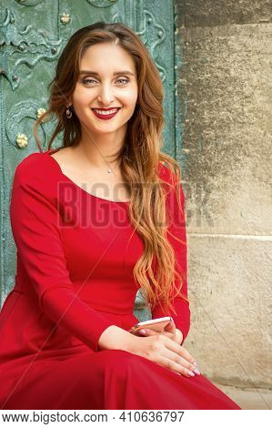Portrait Of A Beautiful Young Caucasian Traveling Woman Sitting At The Door With Smartphone Smiling