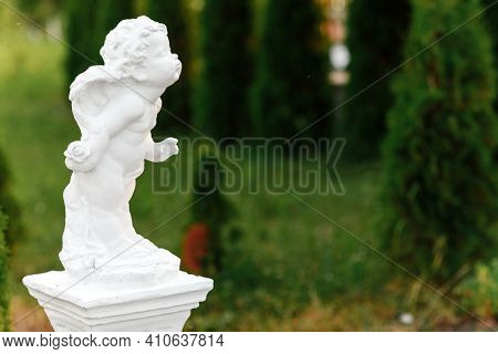 Statue Of Baby Angel With Wings Against Green Garden. The Cute Little Cupid Angel Sculpture Statue S
