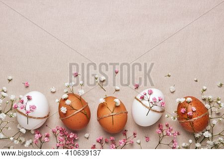 Easter Eggs With Natural Flowers Decor On Linen Background. Zero Waste Easter Concept In Neutral Col