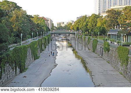 Vienna, Austria - July 11, 2015: Few People Walking Along River At City Park In Wien, Austria.