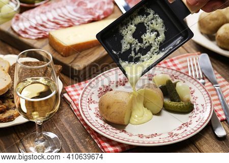 Raclette cheese melted by raclette pan is putting on freshly boiled potatoes.
