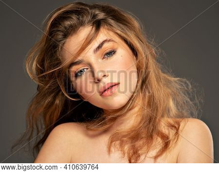 Closeup portrait of an young adult girl with long curly hair.  Photo of a fashion model posing at studio. Pretty young woman with long brown hair looking at camera. Beauty portrait.