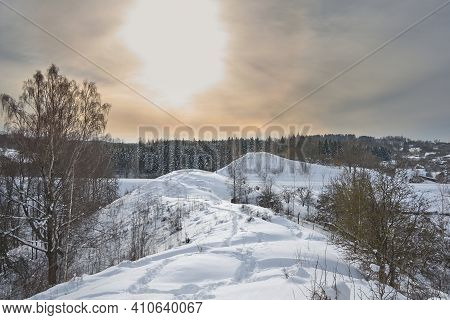 Snowdrifts On Winter Snow Covered Small Hills, Trees And Sun Shine Glow In Yellow-blue Sky.