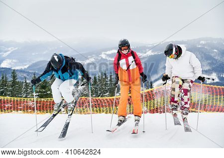 Full Length Of Skiers Team In Ski Jackets And Helmets Skiing In Winter Snowy Mountains, Making Jump