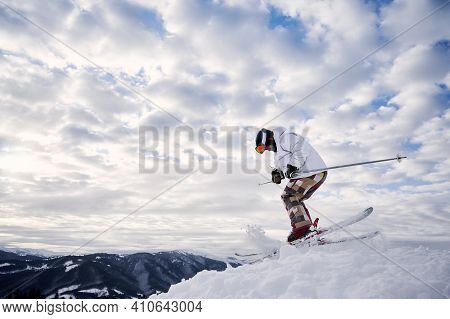 Side View Of Male Skier In Winter Jacket Sliding Down Snow-covered Slopes On Skis Under Beautiful Cl