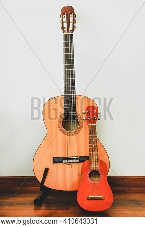 Classic Six-string Wooden Guitar And Hawaiian Four-string Guitar Ukulele Stand Against The Wall. Com