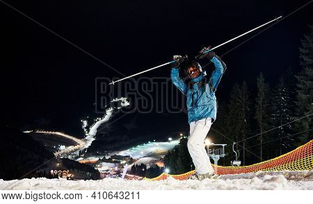 Skier Keeping His Hands Up, Standing On Hill Getting Ready For A Night Ride. Beautiful Illuminated S